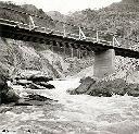 Pont sur la Kyimbi menant à la centrale au pied de la montagne